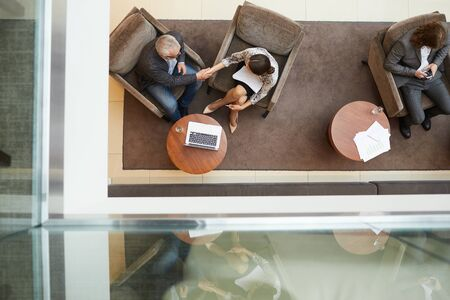 Top view background of waiting room or office lobby with business people shaking hands siting comfortable chairs, copy space Stockfoto