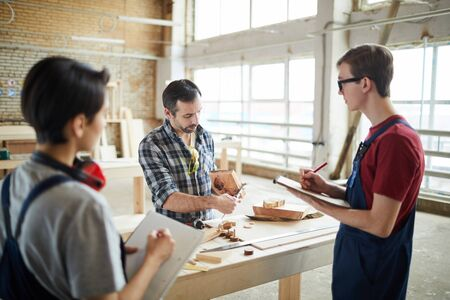 Waist up portrait of mature carpenter teaching young apprentices in workshop Stock Photo