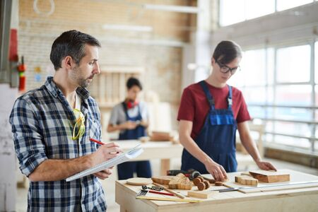 Waist up portrait of mature carpenter holding clipboard d and taking notes while overseeing trainees in workshop class, copy space Stock Photo