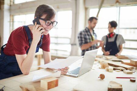 Retrato de carpinteros modernos que trabajan en la fábrica de carpintería, se centran en un joven sonriente hablando por teléfono y usando la computadora portátil en primer plano, espacio de copia