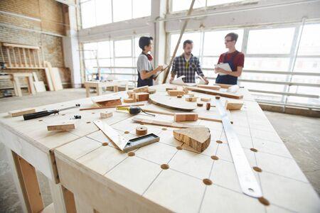 Brede hoekmening bij een groep hedendaagse timmerlieden die een project bespreken in een houtbewerkingswinkel, kopieer ruimte Stockfoto