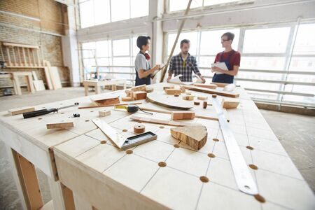 Wide angle view at group of contemporary carpenters discussing project in woodworking shop, copy space Standard-Bild
