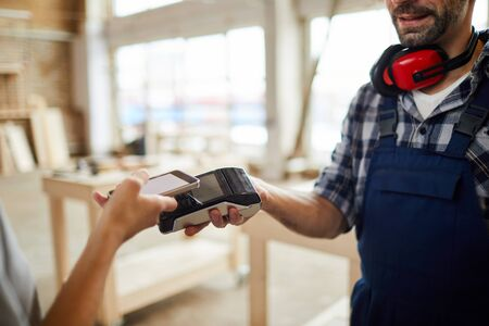 Closeup of unrecognizable customer paying via NFC in joinery shop, copy space