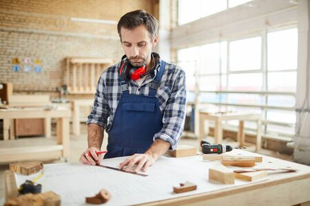 Waist up portrait of mature carpenter marking wood while building handmade furniture in workshop, copy space Stockfoto