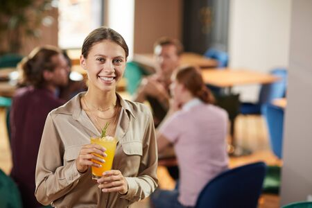 Waist up portrait of cheerful young woman looking at camera while holding refreshing drink in cafe, copy space Stok Fotoğraf