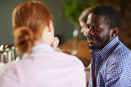 Portrait of African-American man talking to young woman while sitting with group of friends at table in cafe, copy space Imagens