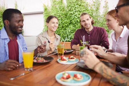 Portrait of multi-ethnic group of friends enjoying lunch together sitting at table in cage and laughing happily, copy space Imagens