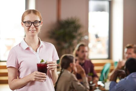 Warm toned waist up portrait of modern young woman smiling at camera while holding drink in cafe, copy space