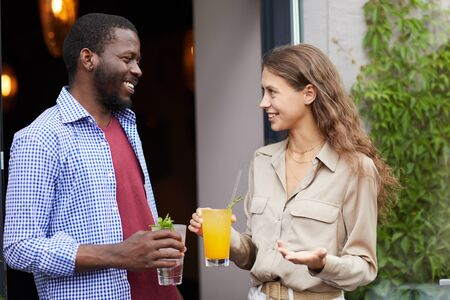 Waist up portrait of smiling young woman talking to African-American man outdoors, both holding cold refreshing drinks, copy space