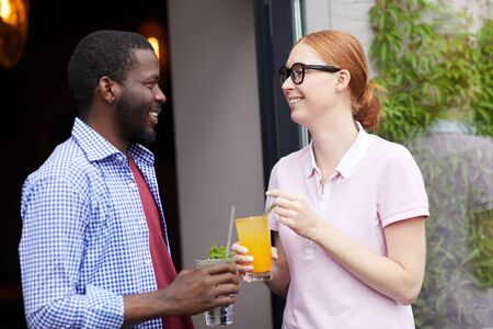 Waist up portrait of smiling young woman talking to African man outdoors, both holding cold refreshing drinks, copy space Imagens