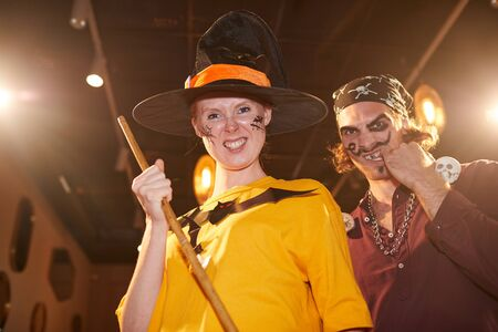 Waist up portrait of adult couple wearing Halloween costumes posing as witch and pirate grimacing at camera during party, copy space 写真素材