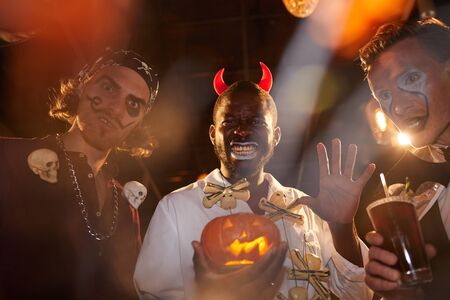 Group of adult men wearing Halloween costumes posing during party in club, focus on African-American man holding pumpkin in center Imagens