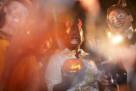 Low angle view at group of adult men wearing Halloween costumes posing during party in club, focus on African-American man holding pumpkin in center Imagens