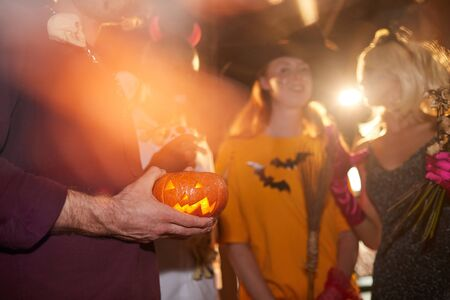 Closeup of unrecognizable man holding carved pumpkin while enjoying Halloween party in nightclub, copy space background