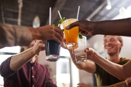 Lage hoek close-up van vrienden die een bril rammelen terwijl ze aan tafel zitten in café genieten van koude verfrissende drankjes, kopieer ruimte Stockfoto
