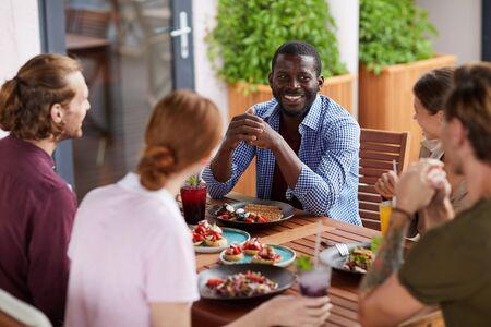 Gruppo multietnico di amici che si godono la cena insieme seduti a tavola e chiacchierano allegramente, si concentrano sull'uomo afroamericano sorridente, copia spazio