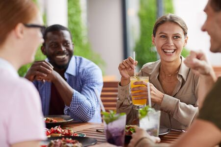 Multi-ethnic group of friends enjoying dinner together sitting at table in cafe and chatting focus on young woman laughing happily holding drink , copy space