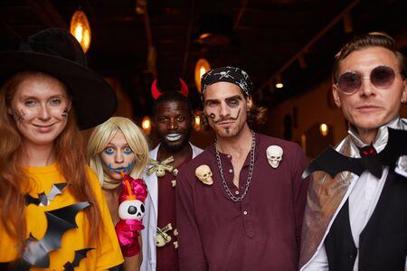 Multi-ethnic group of people wearing Halloween costumes posing looking at camera while enjoying party in nightclub Imagens