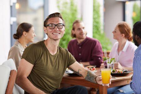 Portret van getatoeëerde hedendaagse man die lacht naar de camera terwijl hij een cocktail vasthoudt aan tafel in café en geniet van een feestdiner met vrienden, kopieer ruimte Stockfoto