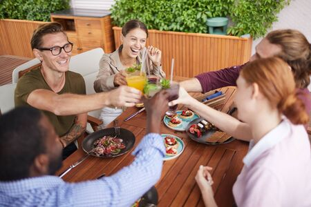 High angle view at group of contemporary people toasting and clinking glasses while celebrating holiday at dinner in cafe, copy space