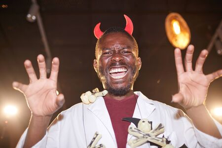 Low angle portrait of African-American man in Halloween costume posing as devil with horns during party , copy space 写真素材