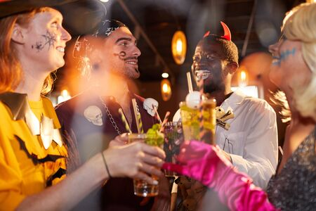 Grupo multiétnico de amigos con disfraces de Halloween bebiendo cócteles mientras disfrutan de la fiesta en el club y se divierten Foto de archivo