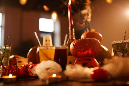 Halloween background of witches table with candles and pumpkins decor set for party in nightclub, copy space
