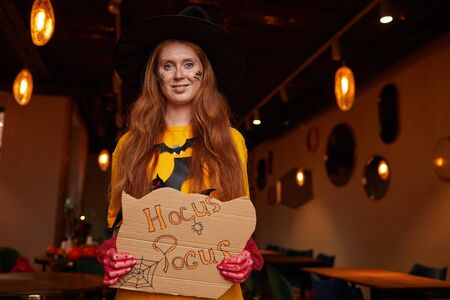 Waist up portrait of red haired woman wearing Halloween costume posing with Hocus Pocus sigh during party in nightclub, copy space