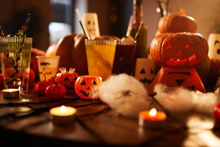 Halloween background of witches table with candles and pumpkins decorations set for party in nightclub, copy space