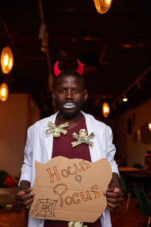 Waist up portrait of African-American man wearing Halloween costume posing with Hocus Pocus sigh during party in nightclub