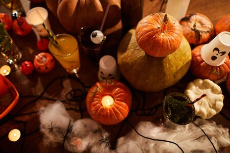 Halloween background, top view of witches table with candles and pumpkins set for party in nightclub, copy space Stock Photo