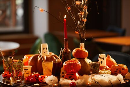 Halloween background of witches table with carved pumpkins decorations set for party in nightclub, copy space
