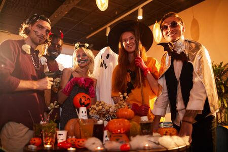 Portrait of adult people wearing Halloween costumes posing making faces at camera during party in nightclub, copy space 스톡 콘텐츠