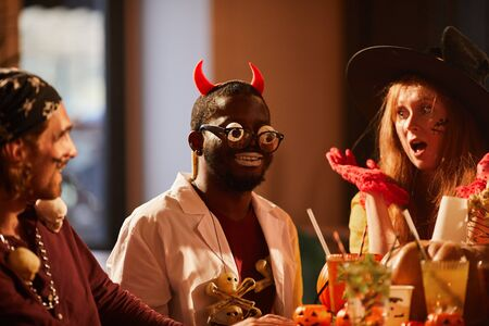 Multi-ethnic group of friends wearing costumes having fun during Halloween party together, copy space