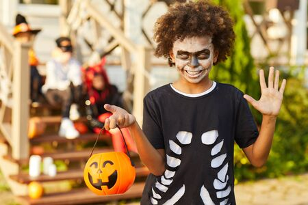 Waist up portrait of African-American boy wearing Halloween costume looking at camera while posing outdoors holding pumpkin basket in trick or treat season, copy space 스톡 콘텐츠