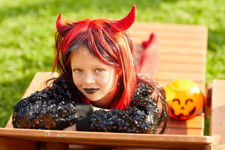 Portrait of cute girl wearing Halloween costume posing outdoors in sunlight while trick or treating, copy space