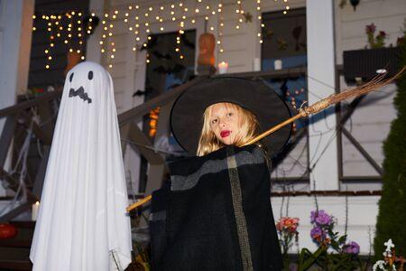 Retrato de lindo poco con posando con escoba de pie junto a casa decorada en halloween, espacio de copia