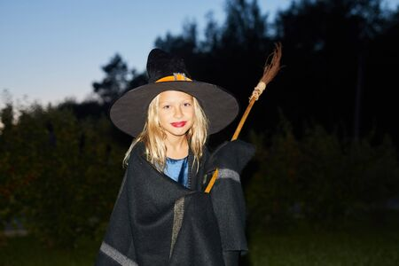 Waist up portrait of cute little witch looking at camera while standing in dark on Halloween, copy space