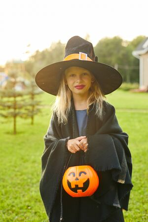 Waist up portrait of cute teenage girl dressed as witch posing outdoors on Halloween and holding trick or treat basket, copy space Banco de Imagens - 130071792