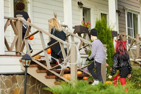 Full length portrait of children trick or treating on Halloween standing on porch, copy space