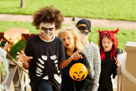 Portrait of multi-ethnic group of children trick or treating on Halloween standing on stairs in row, copy space