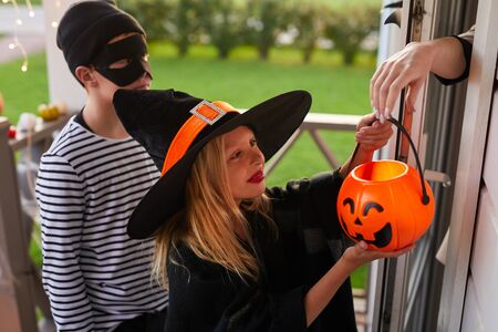 High angle portrait of two childrentaking candy while trick or treating on Halloween, copy space