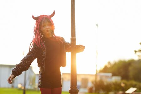 Portrait of cute little girl wearing Halloween costume looking at camera while having fun outdoors in sunlight, copy space 版權商用圖片