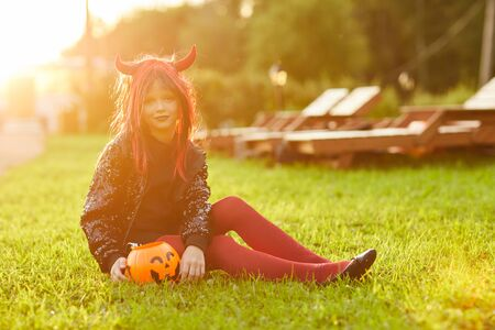 Full length portrait of cute little girl wearing Halloween costume sitting on green lawn with pumpkin basket and looking at camera, copy space 版權商用圖片 - 130072528