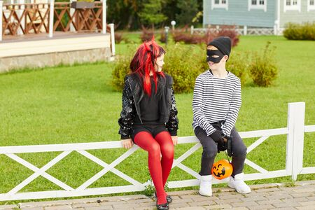 Full length portrait of two happy little kids wearing Halloween costumes sitting on fence while trick or treating, copy space