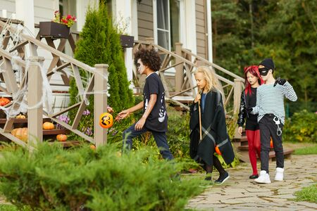 Full length portrait of group of children trick or treating on Halloween walking door to door, copy space Stock Photo