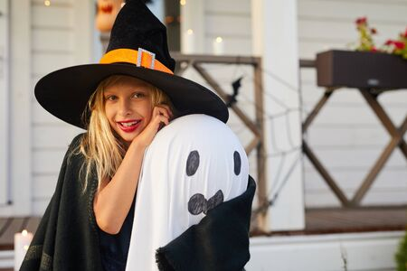 Waist up portrait of cute little girl wearing witch costume looking at camera while posing by house on Halloween, copy space