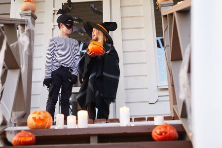 Low angle portrait of two children, boy and girl, standing on porch of decorated house while trick or treating on Halloween, copy space Фото со стока