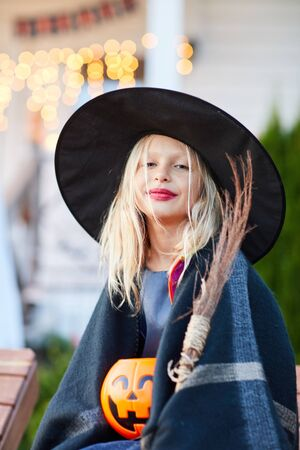 Portrait of smiling little girl wearing witch costume looking at camera on Halloween day, copy space