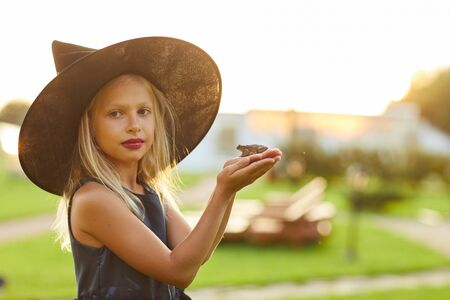 Waist up portrait of cute little witch holding frog while posing outdoors on Halloween, copy space Banco de Imagens
